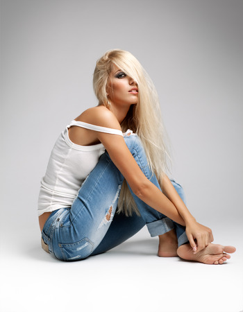 jean: Blonde young woman in ragged jeans and vest sitting on floor on gray background Stock Photo