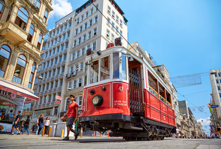 ISTANBUL, TURKEY - JULY 13, 2014:  Heritage trams of a Taksim-Tunel Nostalgia Tramway line operates on Istiklal Street between Taksim Square and underground railway line - Tunnel.  Istanbul, Turkey Editorial