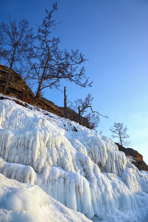 baical: Rocks covered by icicles on winter siberian Baikail lake unber blue sky at evening time