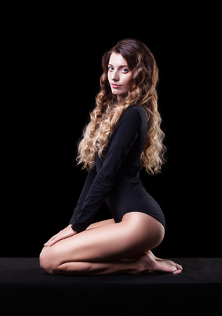legs crossed at knee: Portrait of beautiful caucasian model posing on black cloth in body on black background