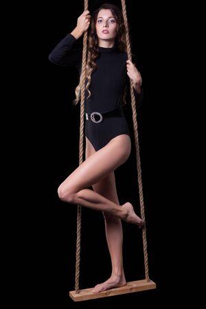 jungen unterwäsche: Portrait der schönen kaukasischen Model posiert auf Seil schwingen im Körper Kleid auf schwarzem Hintergrund