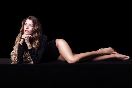 legs crossed on knee: Portrait of beautiful caucasian model laying on black cloth in body on black background