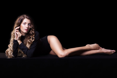 legs crossed at knee: Portrait of beautiful caucasian model laying on black cloth in body on black background