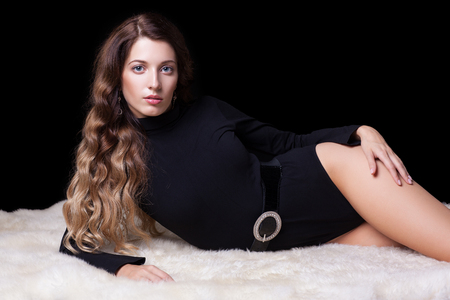 black fashion model: Portrait of beautiful caucasian model posing on white furs in body on black background