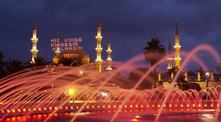 camii: The view of Blue mosque throught the fountain water in the evening illumination. Traditional mahya lights are stretched across the minarets during the holy month of Ramadan, Istanbul, Turkey