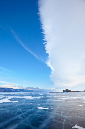 global cooling: Winter ice landscape on Siberian lake Baikal with dramatic weather clouds front before the Storm