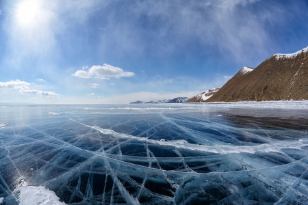 arctic landscape: Wide angle shot of winter ice landscape on Siberian lake Baikal with dramatic weather clouds on blue sky background