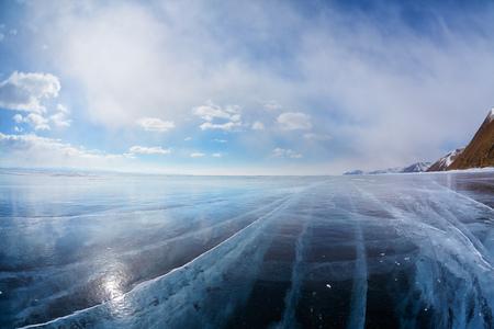 to wind: Amplio ángulo de disparo del paisaje de hielo en invierno siberiano Baikal lago con espectaculares nubes tiempo en el fondo de cielo azul