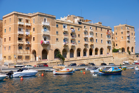 residental: The view of residental houses on the end of Senglea L-isla peninsula with the traditional Maltese boats moored in the harbor. Malta.