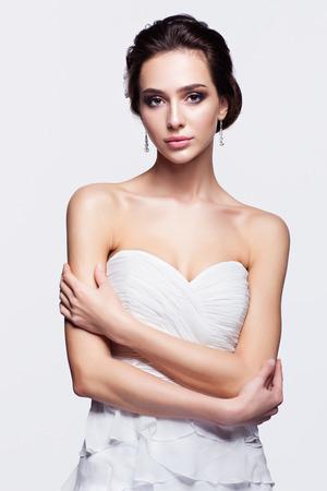 Portrait de mariée belle jeune femme brune en robe de mariée blanche avec les mains croisées sur fond gris clair