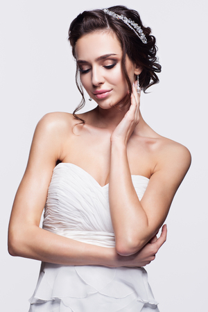 brown skin: Portrait of beautiful young brunette woman bride with hand near face in white Wedding Dress on light gray background