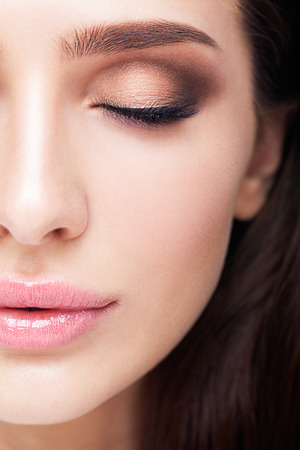 maquillaje de ojos: cara femenina retrato de la belleza con el maquillaje en la mitad aqua lapa Shell sombras de color de ojos, delineador de color azul del tubo respirador y los labios de cuarzo rosa