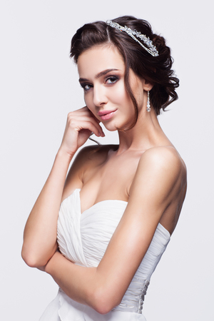 Portrait of beautiful young brunette woman bride with hand near face in white Wedding Dress on light gray background