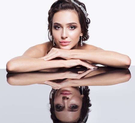 posing: Portrait of young beautiful brunette woman sitting at mirror table on light gray background Stock Photo
