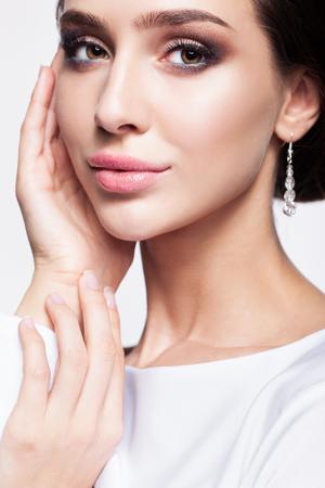 Portrait de la belle jeune femme brune mariée avec les mains près de visage en blanc robe de mariée sur fond gris clair