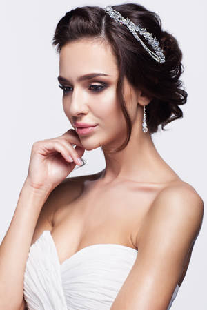 decollete: Portrait of beautiful young brunette woman bride with hand near face in white Wedding Dress on light gray background