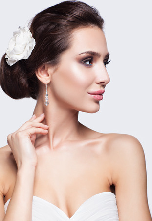 bridal makeup: Portrait of beautiful young brunette woman bride in white Wedding Dress on light gray background