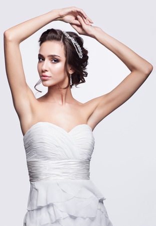woman hands up: Portrait of beautiful young brunette woman bride in white Wedding Dress with hands up on light gray background
