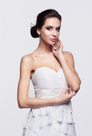 Portrait of beautiful young brunette woman bride with hands near face in white Wedding Dress on light gray background