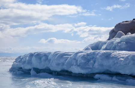 floe: Rocks covered by ice on winter siberian Baikail lake under blue sky backgroun Stock Photo