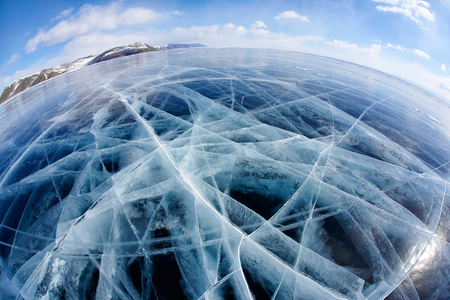 global cooling: Wide angle shot with fisheye lens of winter ice landscape on Siberian lake Baikal with dramatic weather clouds on blue sky background Stock Photo