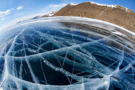 baical: Wide angle shot with fisheye lens of winter ice landscape on Siberian lake Baikal with dramatic weather clouds on blue sky background Stock Photo