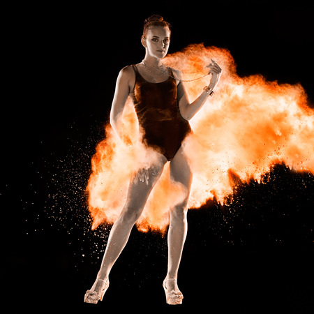 strew: Young woman jumping in fire red powder cloud on black background Stock Photo