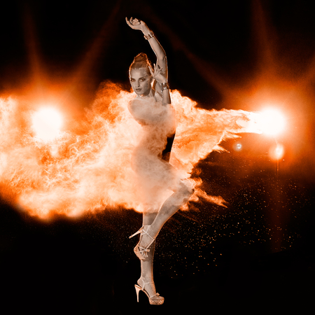 Saltar joven mujer en el fuego nube de polvo rojo sobre fondo negro Foto de archivo