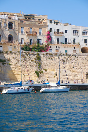 residental: SENGLEA, MALTA - JULY 31, 2015: Residental houses on the end of Senglea I-isla peninsula with the traditional Maltese boats moored in the harbor. Malta