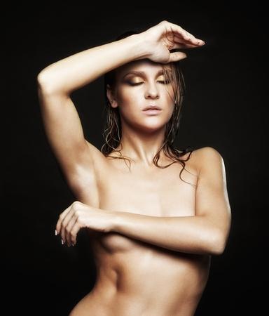 femme noire nue: Portrait de la belle jeune femme nue avec éclat humide maquillage et les yeux fermés sur fond noir Banque d'images