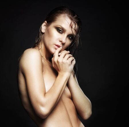 young woman nude: Portrait of young beautiful nude woman with wet shining  makeup  on black background