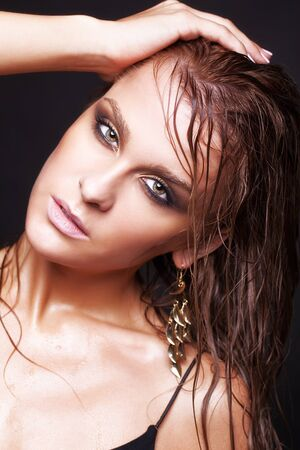 ojos marrones: Retrato de joven bella mujer con maquillaje brillante húmedo sobre fondo negro Foto de archivo