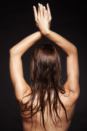 femme noire nue: Portrait of young wet nude beautiful woman from back side  on black background Banque d'images