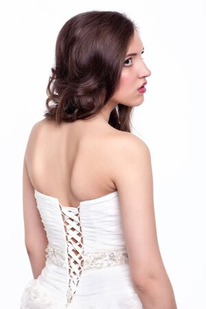 faceart: Portrait of beautiful young brunette woman bride in white Wedding Dress from back side on light gray background