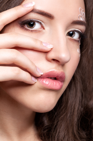 french model: Close-up portrait of beautiful young woman with face art  make up and manicure Stock Photo
