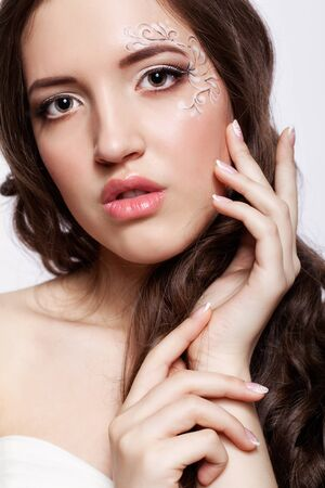 faceart: Close-up portrait of beautiful young woman with face art  make up and manicure Stock Photo
