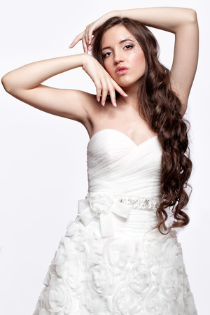 faceart: Portrait of beautiful young brunette woman bride in white Wedding Dress on light gray background