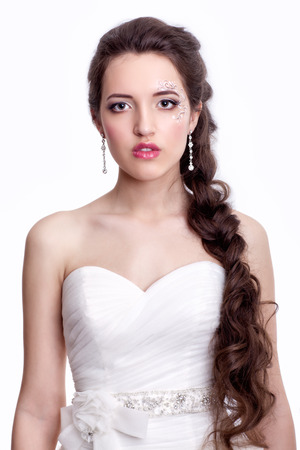 ear ring: Portrait of beautiful young brunette woman bride in white Wedding Dress on light gray background