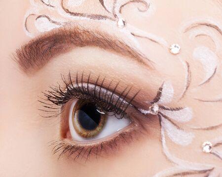 face shot: Close-up shot of beautiful young woman eye with face art  make up