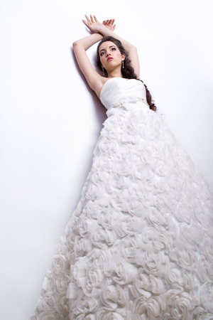 faceart: Portrait of beautiful young woman bride  in white Wedding Dress near light gray wall Stock Photo
