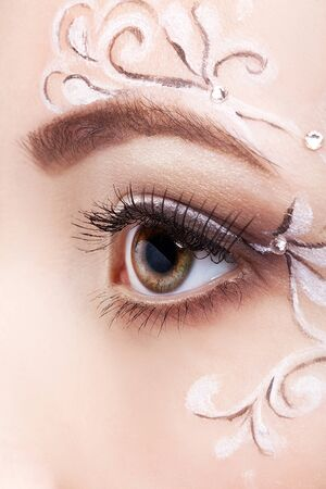 faceart: Close-up shot of beautiful young woman eye with face art  make up