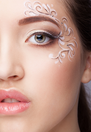 faceart: Close-up portrait of beautiful young woman with face art  make up