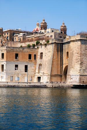 dockyard: The view of historical buildings of Senglea city with Sheer Bastion and Isla Basilica over the Dockyard creek from Birgu. Malta.