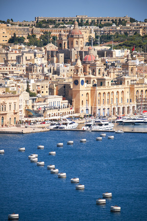 bordering: The view of Birgu peninsula (Vittoriosa city) with the buoy line in the Grand Harbour from the bordering terrace of the Upper Barrakka Gardens. Malta Stock Photo