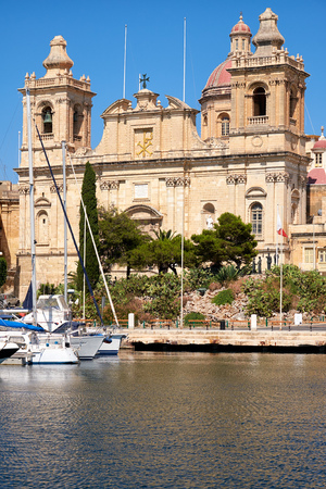 ship order: The view of Collegiate church of St Lawrence over the water of Dockyard creek. The church of St Lawrence  is an Orders of Saint John first Conventual Church  situated in Birgu in Malta. Stock Photo