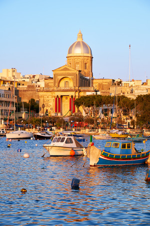 st  joseph: The view of  St Joseph church on the shore and a traditional maltese boats (Luzzu) in the Kalkara bay between Birgu and Kalkara peninsular, Malta. Stock Photo