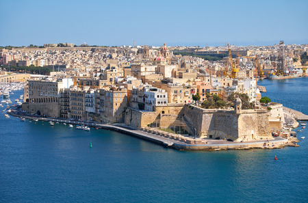bordering: The view of Grand Harbour and Senglea (L-isla) peninsula  with  Fort Saint Michael on the tip from the bordering terrace of the Upper Barrakka Gardens. Malta