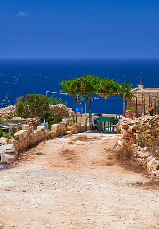 south coast: Old maltese bungalow yard with stone fence and vine-covered canopy on south coast of Malta island