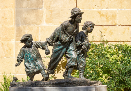 miserable: Valletta, MALTA - JULY 24, 2015: Sculpture of Gavroshe  with brothers in the Upper Barrakka Gardens - replica of the statue of Victor Hugos novel character by Maltese sculptor Antonio Sciortino.