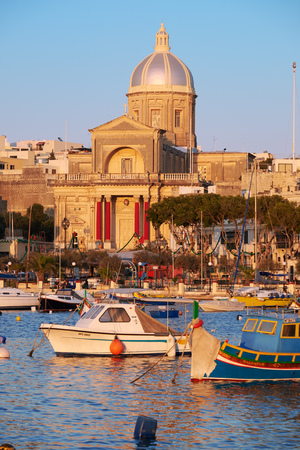 st  joseph: Kalkara, MALTA - JULY 24, 2015: The view of  St Joseph church on the shore and a traditional maltese boats (Luzzu) in the Kalkara bay between Birgu and Kalkara peninsular, Malta. Editorial
